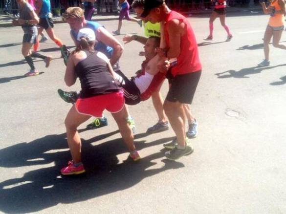 A runner carried over the finish line of the Boston Marathon by other competitors when he collapsed just 100 meters before the end.